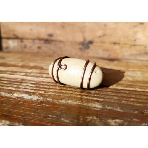 Wired -sormus beigen värisellä rantakivellä
